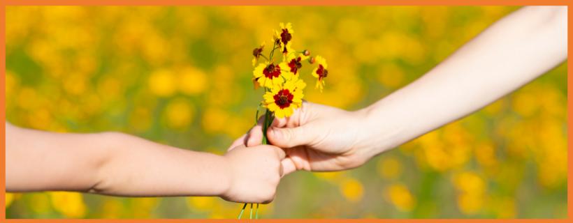 lapsi antaa aikuiselle kukkakimppua